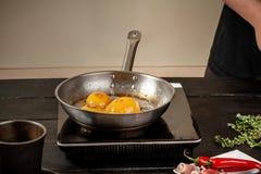 Pêssegos em uma bandeja de fritada Pêssegos do amarelo do fruto enlatado, fundo de madeira preto, placa Imagem de Stock