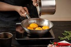 Pêssegos em uma bandeja de fritada Pêssegos do amarelo do fruto enlatado, fundo de madeira preto, placa Fotografia de Stock Royalty Free