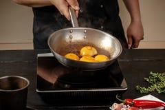 Pêssegos em uma bandeja de fritada Pêssegos do amarelo do fruto enlatado, fundo de madeira preto, placa Fotografia de Stock
