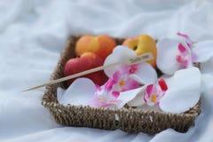 Pêssegos em uma cesta com as flores na grama fotografia de stock royalty free