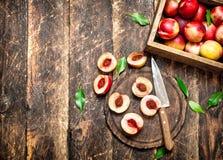 Pêssegos maduros em uma placa de corte Fotografia de Stock