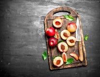 Pêssegos maduros em uma placa de corte com uma faca Imagens de Stock Royalty Free