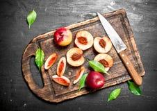 Pêssegos maduros em uma placa de corte com uma faca Foto de Stock