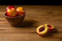 Pêssegos maduros frescos em uma placa marrom, a tabela de madeira Foto de Stock