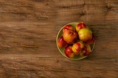 Pêssegos maduros frescos em uma placa verde, a opinião de tampo da mesa de madeira Fotografia de Stock Royalty Free