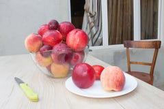 Pêssegos, nectarina e ameixas suculentos na mesa de cozinha Fruto na tabela Foto de Stock