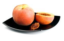 Pêssegos vermelhos com a semente no prato preto Imagem de Stock Royalty Free