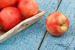 Pêssegos vermelhos maduros na bandeja na tabela de madeira azul Foto de Stock