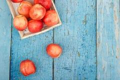 Pêssegos vermelhos maduros na bandeja na tabela de madeira azul Imagem de Stock Royalty Free