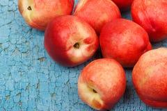 Pêssegos vermelhos maduros na tabela de madeira azul Imagem de Stock