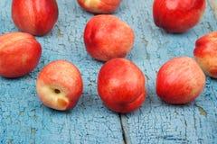 Pêssegos vermelhos maduros na tabela de madeira azul Foto de Stock Royalty Free