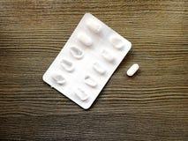 Píldora aislada al lado del paquete de píldoras imágenes de archivo libres de regalías
