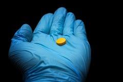 Píldora amarilla en la palma en un guante médico azul en un fondo negro foto de archivo
