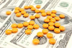 Píldora anaranjada en el dinero Foto de archivo