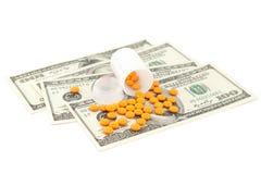 Píldora anaranjada en el dinero Fotos de archivo libres de regalías