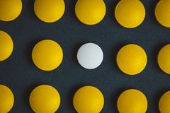 Píldora blanca única de la medicina entre muchas amarillas Soporte fuera de una muchedumbre, de una individualidad y de un concep foto de archivo