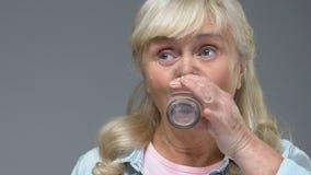 Píldora blanca de la vitamina de la prueba mayor de la mujer y agua potable del vidrio, tratamiento metrajes