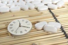 Píldora blanca y reloj numérico romano Imagenes de archivo