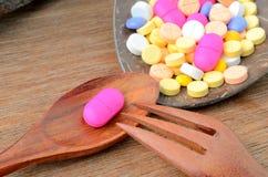 Píldora de la cápsula de la medicina en la cuchara con la bifurcación Foto de archivo libre de regalías