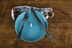 Píldora de la dieta del concepto de la pérdida de peso en la placa con una cinta métrica Foto de archivo libre de regalías