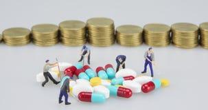 Píldora de la medicina con lapso de tiempo del paso de las monedas de la miniatura y de oro almacen de metraje de vídeo