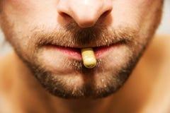 Píldora en su boca Foto de archivo libre de regalías
