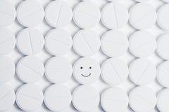 Píldora feliz rodeada por las píldoras blancas de la prescripción Imágenes de archivo libres de regalías
