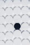 Píldora negra rodeada por las píldoras blancas de la prescripción en el fondo blanco Imágenes de archivo libres de regalías