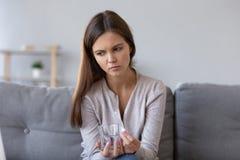 Píldora y vaso de agua pensativos frustrados de la tenencia de la mujer foto de archivo