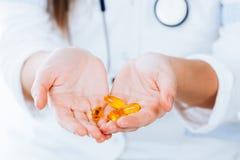 Píldoras amarillas en manos imágenes de archivo libres de regalías