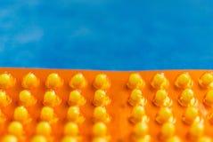 Píldoras amarillas en una ampolla en un fondo azul Imagen de archivo