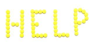 Píldoras amarillas que deletrean la ayuda de la palabra Imagen de archivo libre de regalías