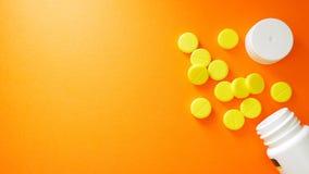 Píldoras amarillas y botella blanca con el espacio de la copia en fondo rojo Concepto sano y de la medicina foto de archivo libre de regalías