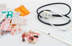 Píldoras, ampollas y un estetoscopio Fotos de archivo
