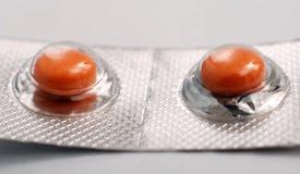 Píldoras anaranjadas de la medicina Fotografía de archivo