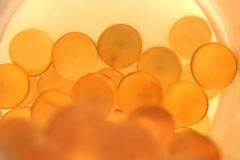 Píldoras anaranjadas en botella Fotos de archivo