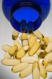Píldoras anaranjadas en vertical azul de la botella Imagen de archivo libre de regalías
