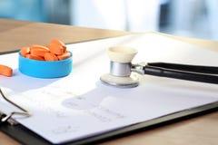 Píldoras anaranjadas, prescripción y phonendoscop en un backgro verde Fotografía de archivo libre de regalías