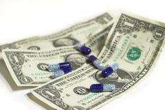 Píldoras azules blancas con las cuentas de un dólar Imagen de archivo libre de regalías