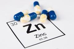 Píldoras azules con el Zn mineral Zincum en un fondo blanco con a fotos de archivo