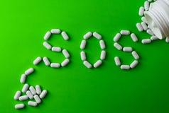 Píldoras blancas en el fondo verde, que formando la palabra - SOS, con una ampolla de píldoras en fondo Imagenes de archivo