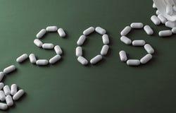 Píldoras blancas en el fondo verde, que formando la palabra - SOS, con una ampolla de píldoras en fondo Foto de archivo libre de regalías