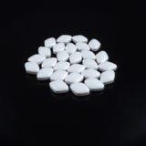 Píldoras blancas en fondo negro Fotos de archivo libres de regalías