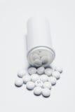 Píldoras blancas que se derraman fuera de una botella de la medicina Foto de archivo