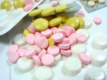 Píldoras blancas y coloreadas de la droga Imagen de archivo libre de regalías