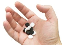 Píldoras blancas y negras en su palma Imagenes de archivo