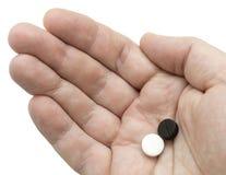 Píldoras blancas y negras en su palma Fotografía de archivo