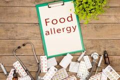 Píldoras, botella médica, jeringuilla, estetoscopio y tablero con el tablero con el texto y x22; Allergy& x22 de la comida; fotos de archivo