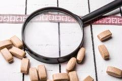 Píldoras, cinta métrica rosada y mano sosteniendo una lupa sobre el fondo de madera blanco Imagen de archivo libre de regalías