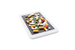 Píldoras coloreadas en la pantalla táctil Foto de archivo libre de regalías